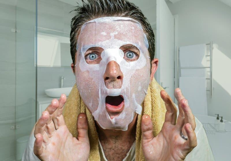 Οι νεολαίες φόβισαν και εξέπληξαν το άτομο χρησιμοποιώντας στο σπίτι την του προσώπου μάσκα εγγράφου ομορφιάς που καθαρίζει που κ στοκ εικόνες με δικαίωμα ελεύθερης χρήσης