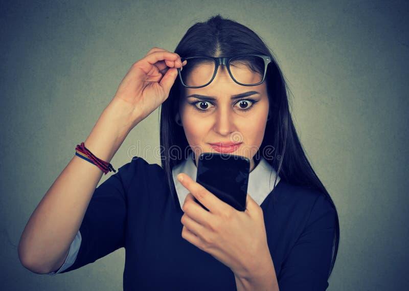 Οι νεολαίες ανατρέπουν την ταραγμένη γυναίκα με τα γυαλιά που εξετάζει το κινητό τηλέφωνο στοκ φωτογραφία
