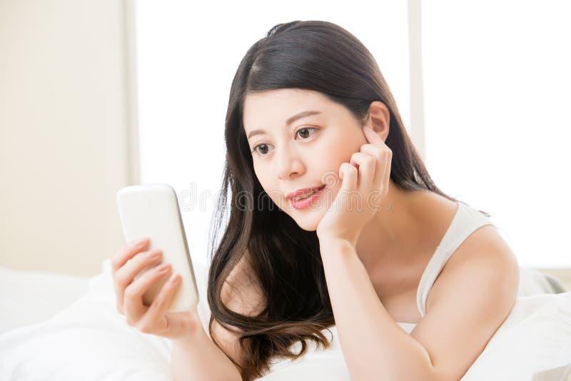 Οι νεολαίες χαμογελούν την ασιατική γυναίκα που διαβάζει το έξυπνο τηλέφωνο στο κρεβάτι στοκ εικόνες με δικαίωμα ελεύθερης χρήσης
