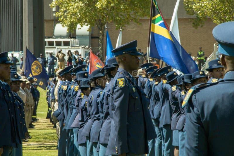 Οι νοτιοαφρικανικές Αστυνομικές Υπηρεσίες στην παρέλαση στο χώρο στο σχηματισμό, πλάγια όψη, σημαία και πετώντας - ευρεία γωνία στοκ εικόνα