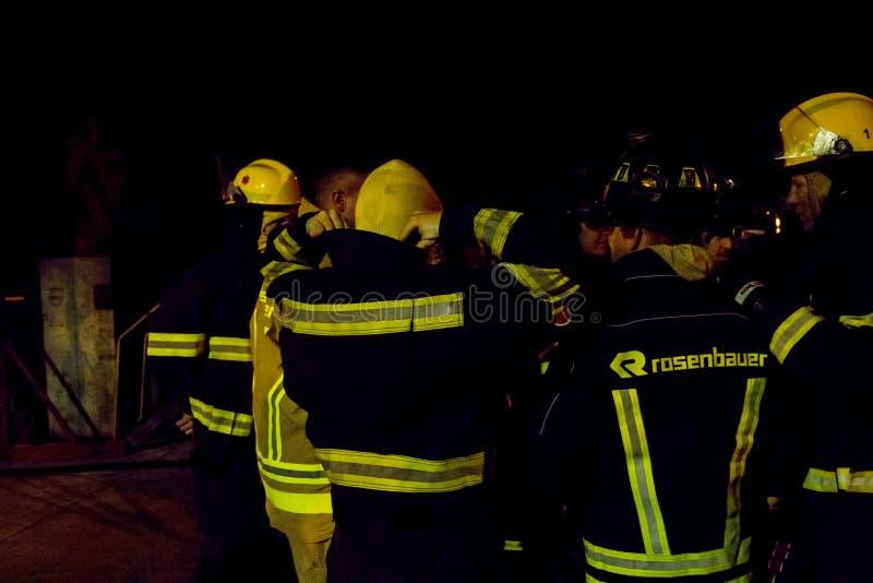 Οι νοτιοαφρικανικοί πυροσβέστες στην αποθήκη συνδέουν τη νύχτα στοκ φωτογραφίες