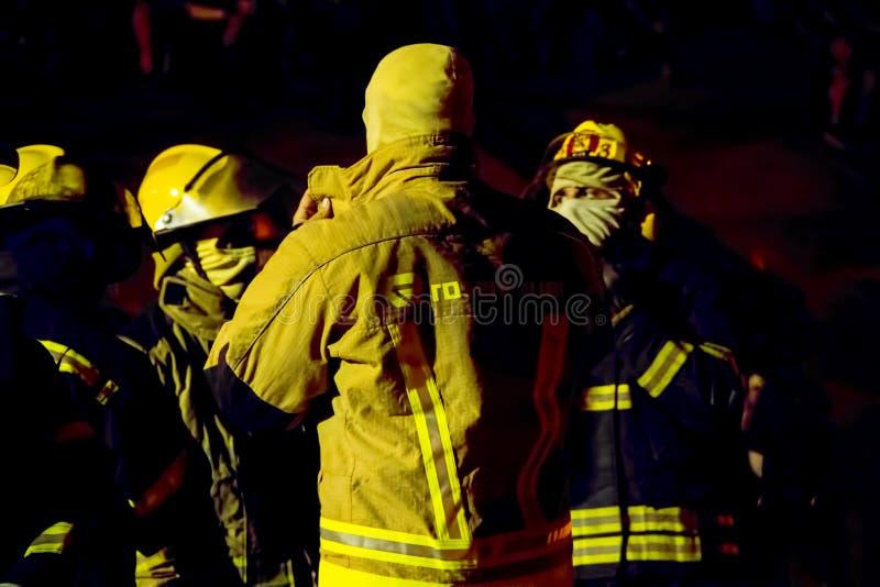 Οι νοτιοαφρικανικοί πυροσβέστες στην πλήρη αποθήκη συνδέουν τη νύχτα στοκ εικόνες