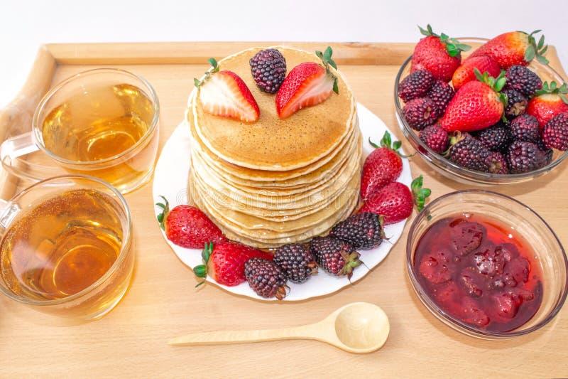 Οι νόστιμες τηγανίτες προγευμάτων με το mora φρούτων, φραουλών και βατόμουρων, έχυσαν το μέλι σιροπιού σε έναν ξύλινο δίσκο στοκ εικόνα