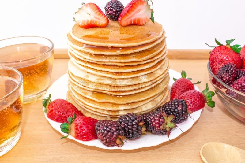 Οι νόστιμες τηγανίτες προγευμάτων με το mora φρούτων, φραουλών και βατόμουρων, έχυσαν το μέλι σιροπιού σε έναν ξύλινο δίσκο στοκ εικόνες