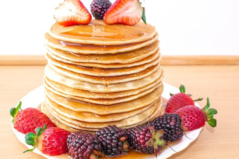 Οι νόστιμες τηγανίτες προγευμάτων με το mora φρούτων, φραουλών και βατόμουρων, έχυσαν το μέλι σιροπιού σε έναν ξύλινο δίσκο στοκ φωτογραφία με δικαίωμα ελεύθερης χρήσης