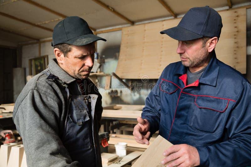 Οι ξυλουργοί συζητούν τα προϊόντα κατασκευής για τα έπιπλα στοκ εικόνες με δικαίωμα ελεύθερης χρήσης
