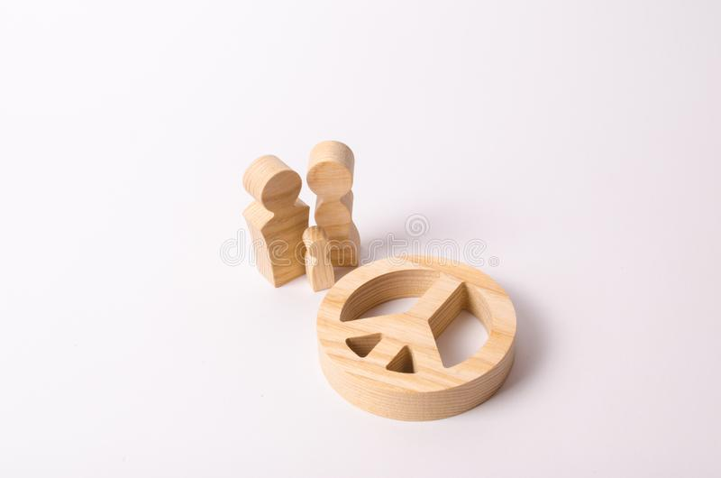 Οι ξύλινοι άνθρωποι ` s τελειώνουν τη στάση κοντά στο σημάδι της ειρήνης, του αφοπλισμού και της ειρηνικής μετακίνησης Η έννοια τ στοκ φωτογραφία με δικαίωμα ελεύθερης χρήσης