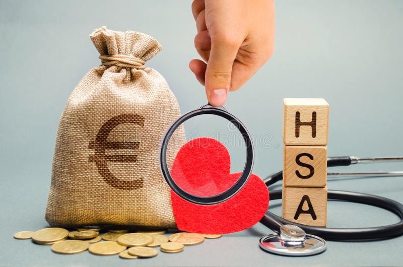 Οι ξύλινοι φραγμοί με τη λέξη ΕΧΟΥΝ και η τσάντα χρημάτων με το στηθοσκόπιο Λογαριασμός ταμιευτηρίου υγείας ( Ασφάλεια υγείας Επε στοκ εικόνες