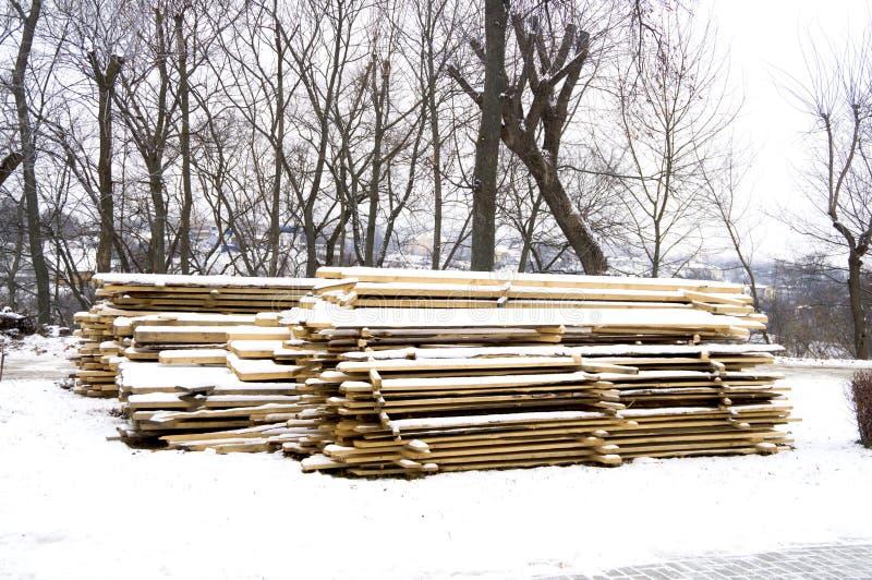 Οι ξύλινοι πίνακες συσσώρευσαν στους σωρούς στο έδαφος και κάλυψαν με το χιόνι στοκ φωτογραφίες με δικαίωμα ελεύθερης χρήσης