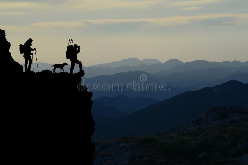 Οι οδοιπόροι βουνών σκιαγραφούν στοκ φωτογραφίες