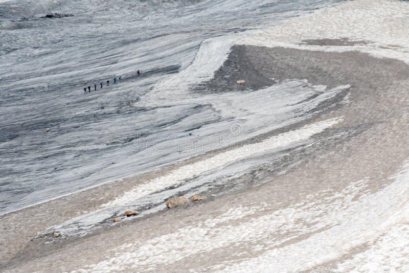 Οι οδοιπόροι περπατούν στον παγετώνα Marmolada στους δολομίτες στοκ εικόνα