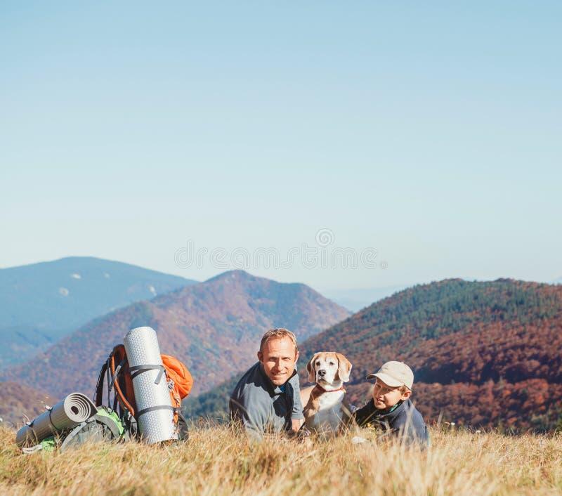 Οι οδοιπόροι backpackers πατέρων και γιων στηρίζονται στο λόφο βουνών με το σκυλί λαγωνικών τους στοκ φωτογραφία με δικαίωμα ελεύθερης χρήσης