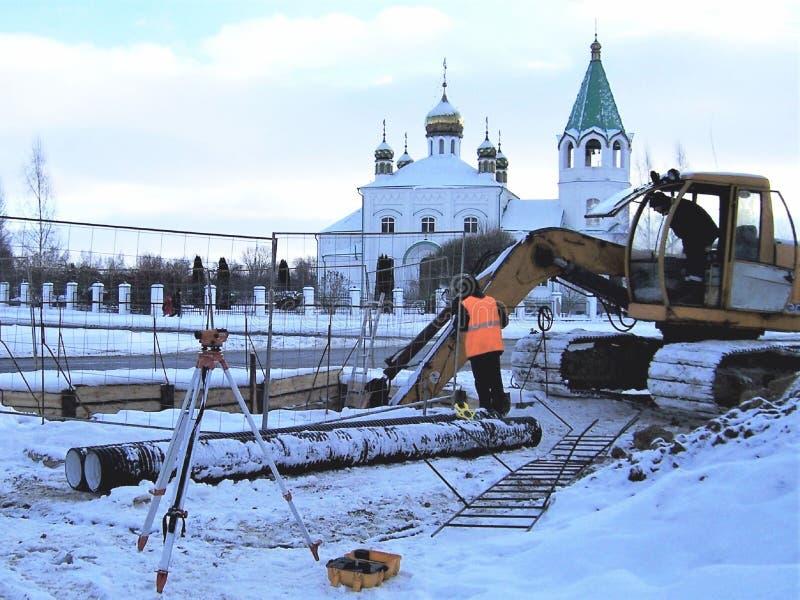 οι οικοδομές, ο εκσκαφέας στην κάμπια στη σειρά μαθημάτων, επισκευή των σωλήνων της θέρμανσης στην πόλη, κοστίζουν το geodeziches στοκ εικόνα με δικαίωμα ελεύθερης χρήσης