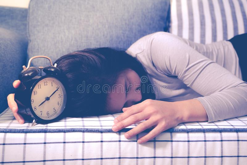 Οι οκνηρές γυναίκες καθορίζουν στον καναπέ μετά από το συναγερμό ρολογιών, αργά ξυπνήστε έννοια τρόπου ζωής στοκ φωτογραφίες με δικαίωμα ελεύθερης χρήσης