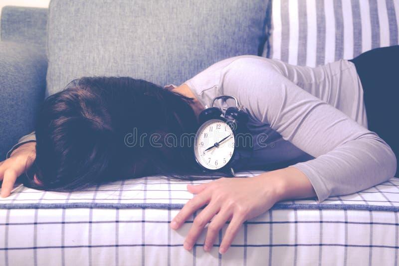 Οι οκνηρές γυναίκες καθορίζουν στον καναπέ μετά από το συναγερμό ρολογιών, αργά ξυπνήστε έννοια τρόπου ζωής στοκ φωτογραφίες
