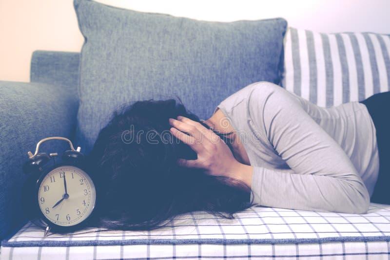 Οι οκνηρές γυναίκες καθορίζουν στον καναπέ μετά από το συναγερμό ρολογιών, αργά ξυπνήστε έννοια τρόπου ζωής στοκ εικόνες με δικαίωμα ελεύθερης χρήσης