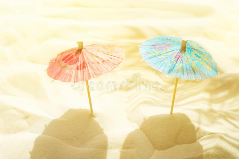 Οι ομπρέλες εγγράφου κοκτέιλ στην άμμο παραλιών στο χρυσό φύλλο φοινικών φωτός του ήλιου σκιάζουν τη σκιαγραφία Δημιουργική καλλι στοκ φωτογραφία