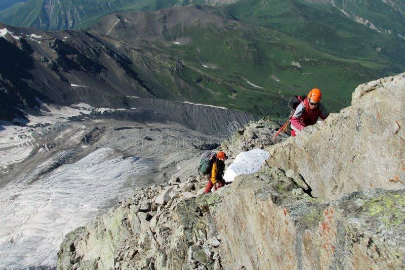 Οι ορειβάτες βράχου στα κράνη στο δύσκολο βουνό καθοδηγούν στοκ εικόνες