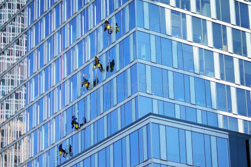 Οι ορειβάτες πλένουν τα παράθυρα και την πρόσοψη γυαλιού του ουρανοξύστη στοκ εικόνες