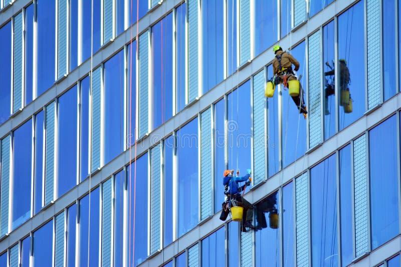 Οι ορειβάτες πλένουν τα παράθυρα και την πρόσοψη γυαλιού του ουρανοξύστη στοκ φωτογραφία