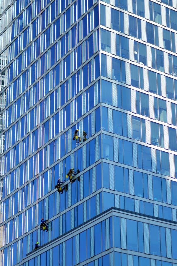 Οι ορειβάτες πλένουν τα παράθυρα και την πρόσοψη γυαλιού του ουρανοξύστη στοκ φωτογραφία με δικαίωμα ελεύθερης χρήσης