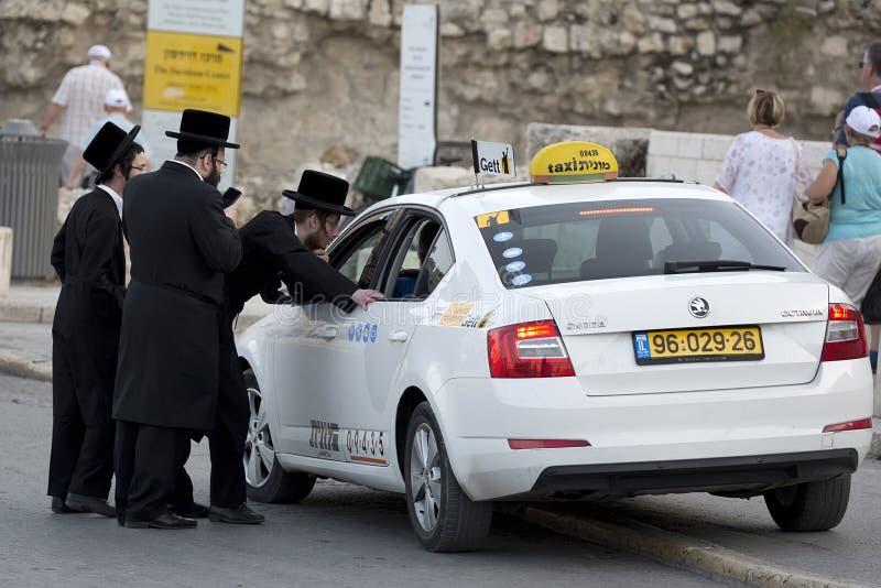 Οι ορθόδοξοι Εβραίοι διατάζουν ένα ταξί στην οδό ` s της Ιερουσαλήμ στοκ φωτογραφία με δικαίωμα ελεύθερης χρήσης