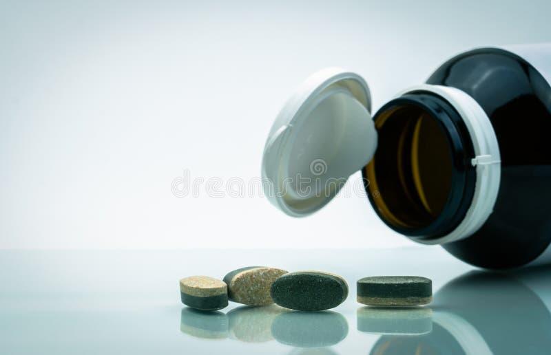 Οι ουσιαστικά βιταμίνες και τα ανόργανα άλατα συμπληρώνουν τα διπλά χάπια ταμπλετών στρώματος και το μπουκάλι γυαλιού ιατρικής με στοκ εικόνες