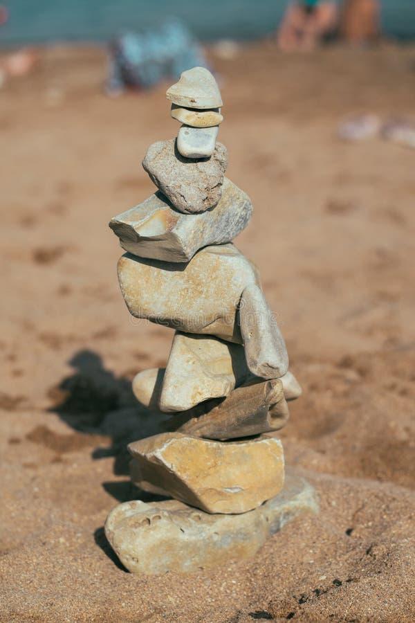 Οι πέτρες βρίσκονται στις πέτρες feng shui στην παραλία Δημιουργία μιας ισορροπίας στην άμμο στοκ εικόνα
