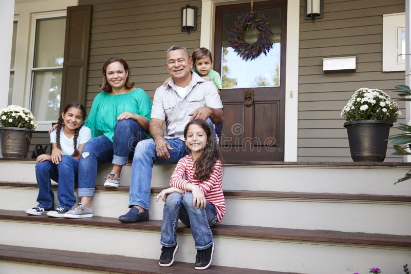 Οι παππούδες και γιαγιάδες με τα εγγόνια κάθονται στα βήματα που καταλήγουν στο σπίτι στοκ εικόνα