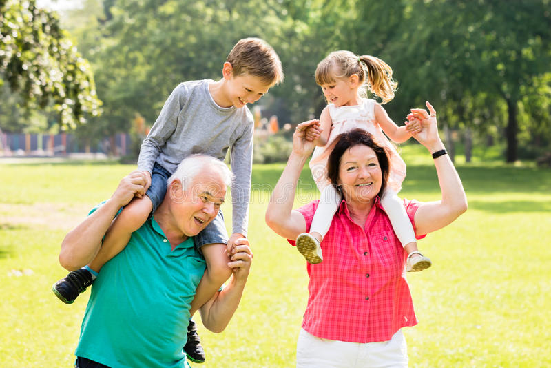 Οι παππούδες και γιαγιάδες που δίνουν τα εγγόνια Piggyback ο γύρος στοκ φωτογραφία με δικαίωμα ελεύθερης χρήσης