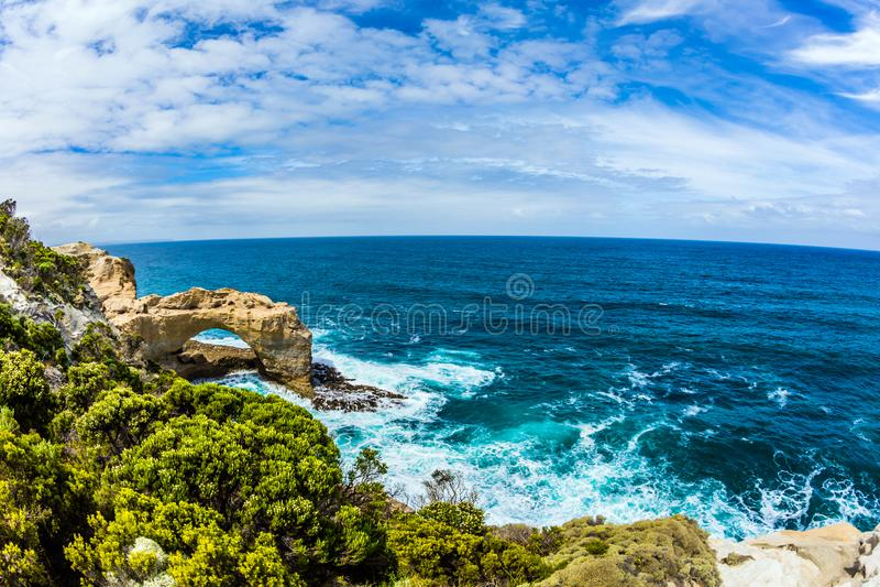 Οι παράκτιοι βράχοι διαμόρφωσαν μια γραφική αψίδα του ψαμμίτη Συντριβή κυμάτων Ειρηνικών Ωκεανών κάτω στην ακτή Η έννοια εξωτικού στοκ εικόνες