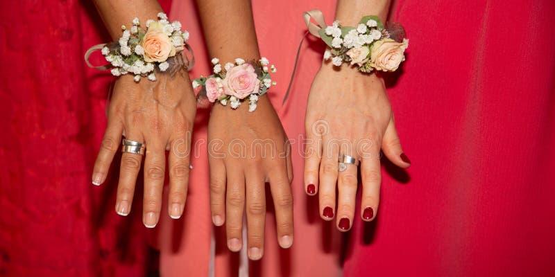Οι παράνυμφοι νυφών με τα κόκκινα ρόδινα βραχιόλια φορεμάτων και λουλουδιών παραδίδουν επάνω το έμβλημα προτύπων εμβλημάτων Ιστού στοκ φωτογραφία με δικαίωμα ελεύθερης χρήσης
