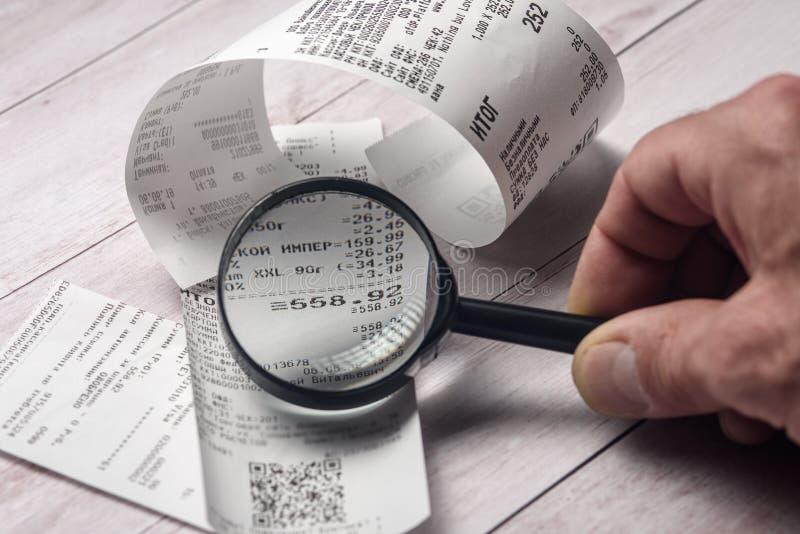 Οι παραλαβές μετρητών στον πίνακα εξετάζονται μέσω μιας ενίσχυσης - γυαλί στοκ εικόνες