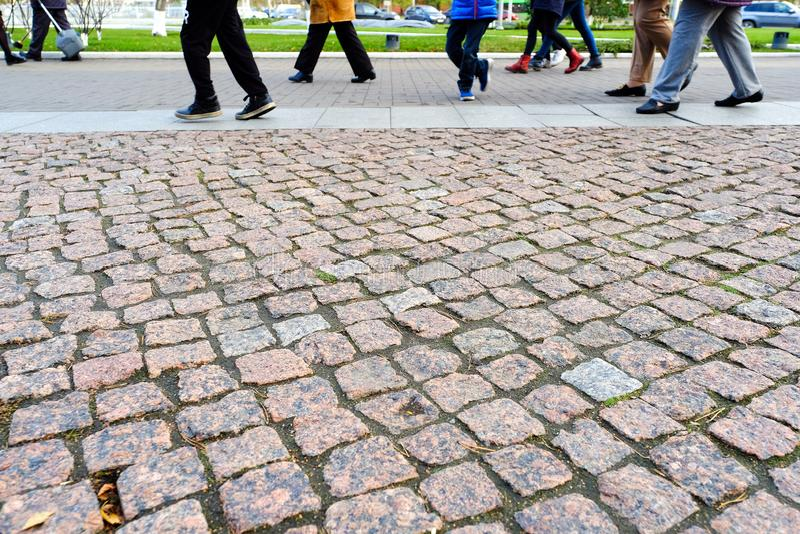 Οι πεζοί περπατούν στο πεζοδρόμιο Αρχαία επίστρωση γρανίτη άποψη κινηματογραφήσεων σε πρώτο πλάνο άνωθεν πεζοδρόμιο στοκ εικόνες