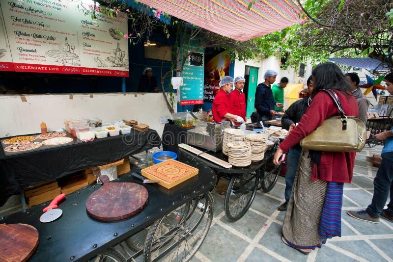 Οι πεινασμένοι άνθρωποι επισκέπτονται το pizzeria στη ζώνη δικαστηρίων τροφίμων στοκ φωτογραφία