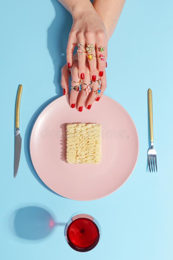 Οι περικοπές κοριτσιών με τα νουντλς μαχαιριών και δικράνων σε ένα ρόδινο πιάτο Έννοια Minimalistic Τοπ όψη στοκ εικόνες με δικαίωμα ελεύθερης χρήσης