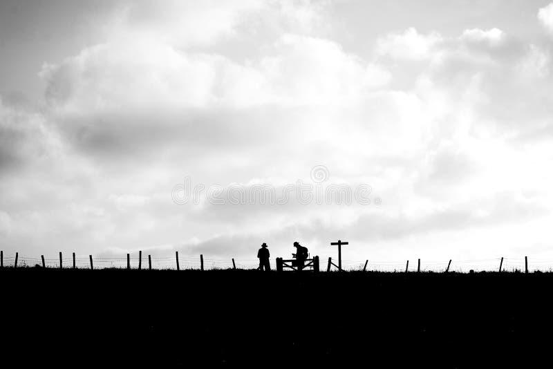 Οι περιπατητές σε ένα σημάδι τοποθετούν σε έναν τομέα στοκ φωτογραφίες