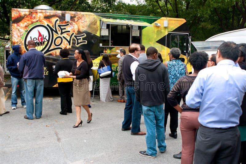 Οι πελάτες στέκονται στη μεγάλη ουρά που διατάζει από τα φορτηγά τροφίμων στοκ εικόνα