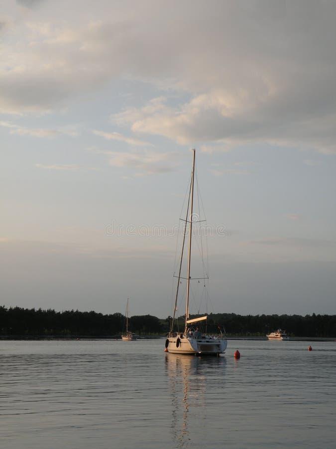 Οι πλέοντας βάρκες και τα γιοτ επιπλέουν σε μια ειρηνική επιφάνεια της theAdriatic θάλασσας, Κροατία, Ευρώπη Στο υπόβαθρο η ακτή  στοκ εικόνες