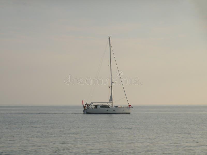Οι πλέοντας βάρκες και τα γιοτ επιπλέουν σε μια ειρηνική επιφάνεια της theAdriatic θάλασσας, Κροατία, Ευρώπη Στο υπόβαθρο η ακτή  στοκ εικόνα