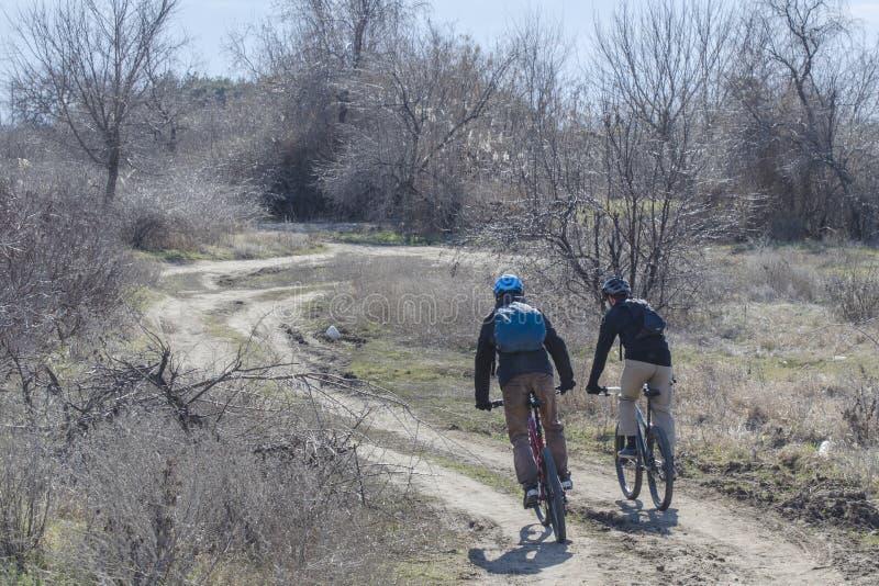 Οι ποδηλάτες οδηγούν τα ποδήλατα σε έναν ανοικτό δρόμο την άνοιξη στοκ φωτογραφίες