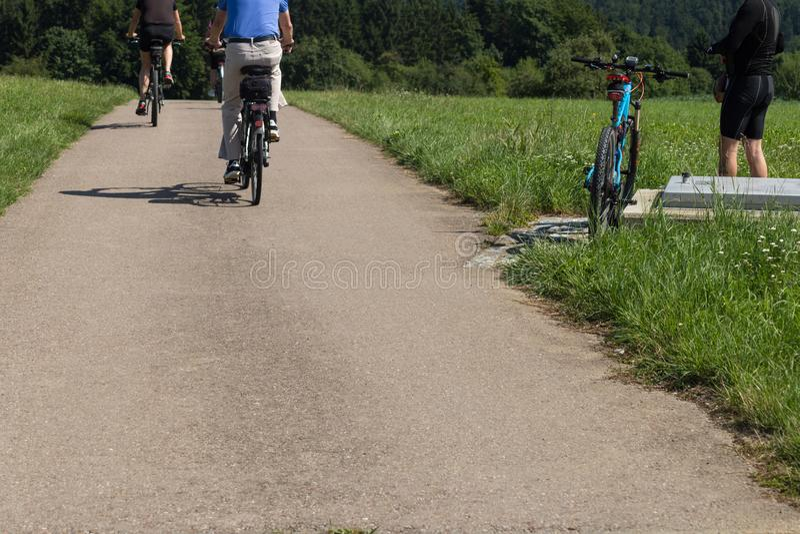 οι ποδηλάτες σε μια απόσταση βλέπουν σε ένα καλοκαίρι ηλιόλουστη ημέρα στοκ εικόνα με δικαίωμα ελεύθερης χρήσης