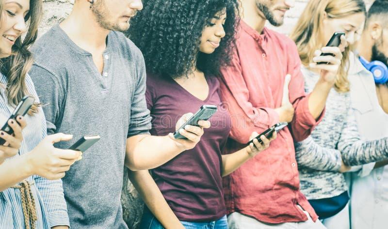 Οι πολυπολιτισμικοί φίλοι ομαδοποιούν τη χρησιμοποίηση του κινητού έξυπνου τηλεφώνου στοκ φωτογραφία με δικαίωμα ελεύθερης χρήσης