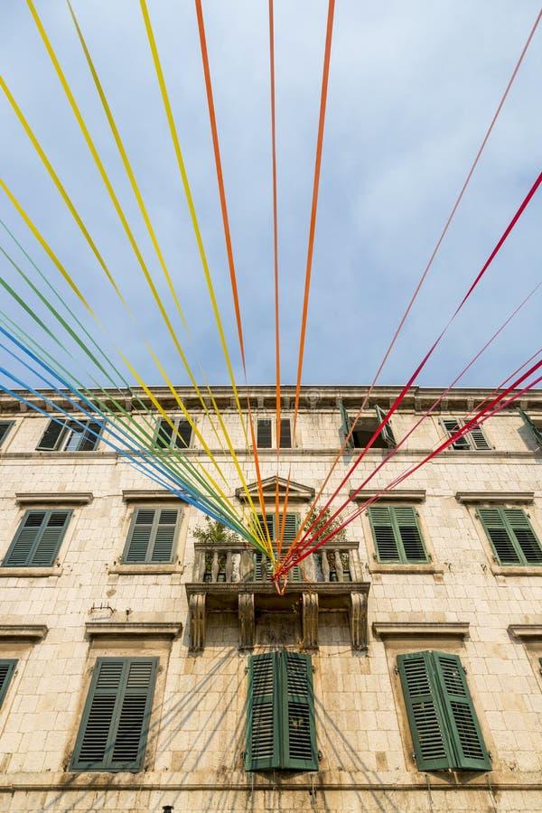 Οι πολύχρωμες κορδέλλες έδεσαν στο μπαλκόνι ενός κατοικημένου κτηρίου ενάντια στον ουρανό στοκ φωτογραφίες