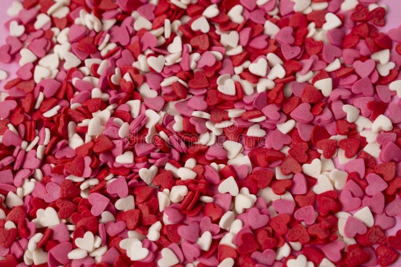 Οι πολύ μικρές καρδιά-διαμορφωμένες καραμέλες είναι διεσπαρμένες πέρα από το υπόβαθρο Πολλές μικρές φωτεινές καρδιές σε μεγάλη πο στοκ εικόνα