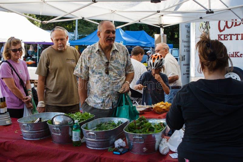 Οι πρεσβύτεροι αγοράζουν την αγορά αγροτών πρασίνων σαλάτας στοκ φωτογραφίες