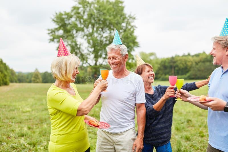 Οι πρεσβύτεροι γιορτάζουν ένα θερινό κόμμα στον κήπο στοκ εικόνες