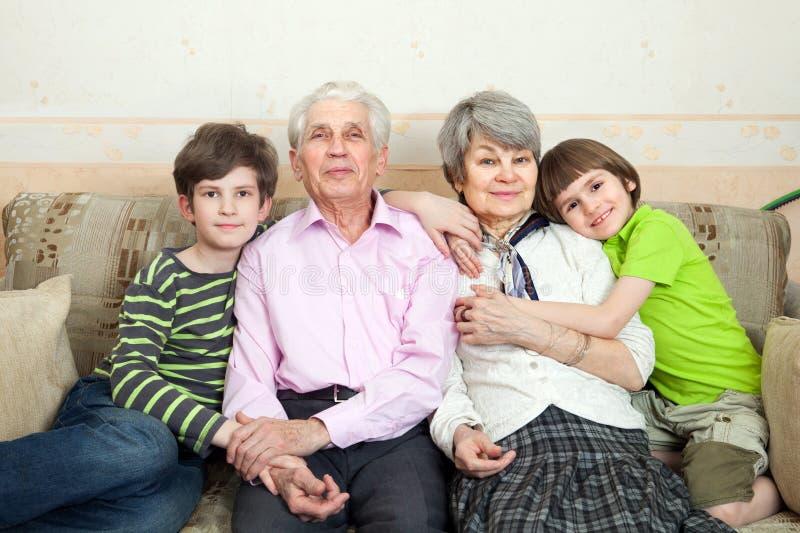 Οι πρεσβύτεροι με τα grandkids κάθονται σε έναν καναπέ στοκ εικόνες