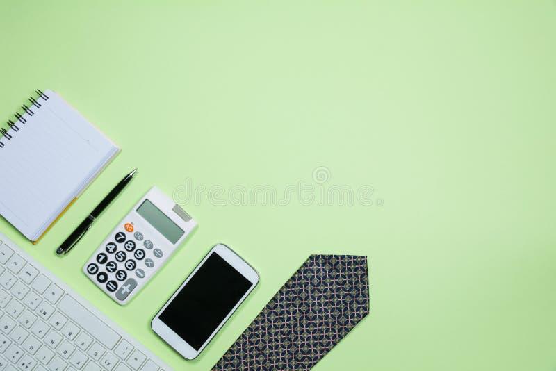 Οι προμήθειες γραφείων στο πράσινο υπόβαθρο με το διάστημα αντιγράφων για το inse στοκ φωτογραφία