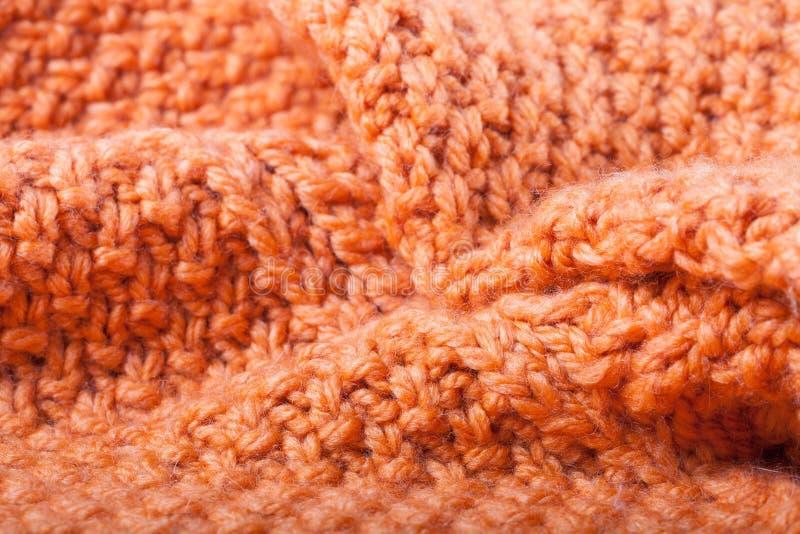 Οι πτυχές του πορτοκαλιού έπλεξαν το μάλλινο πουλόβερ Υπόβαθρο στοκ εικόνες